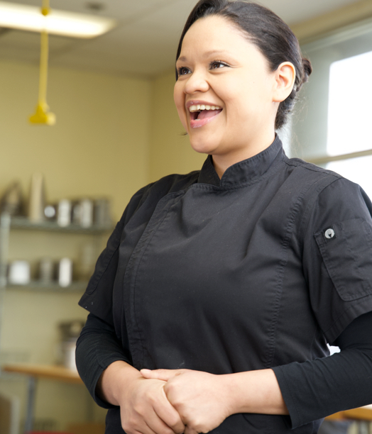 Smiling woman in chef's uniform