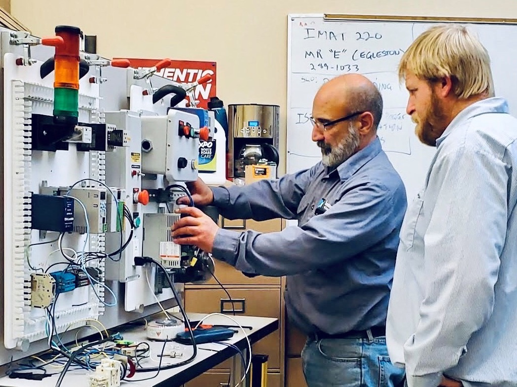 Instructor showing student machinery