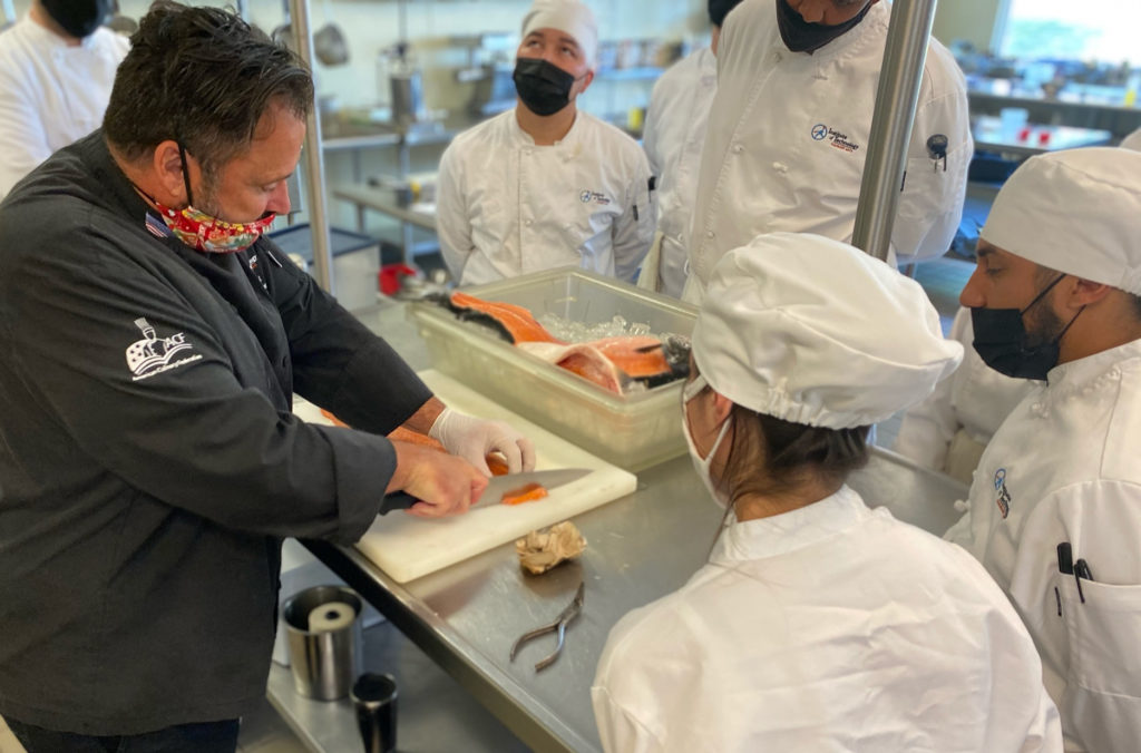 Culinary instructor shows students how to chop vegetables