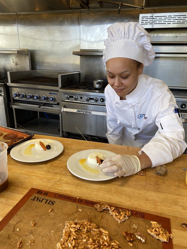 Culinary student finishing a dessert plate