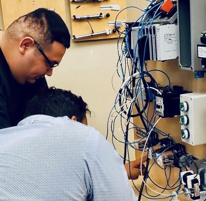 Two men practicing wiring