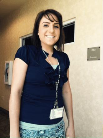 Woman smiling at camera wearing a name tag