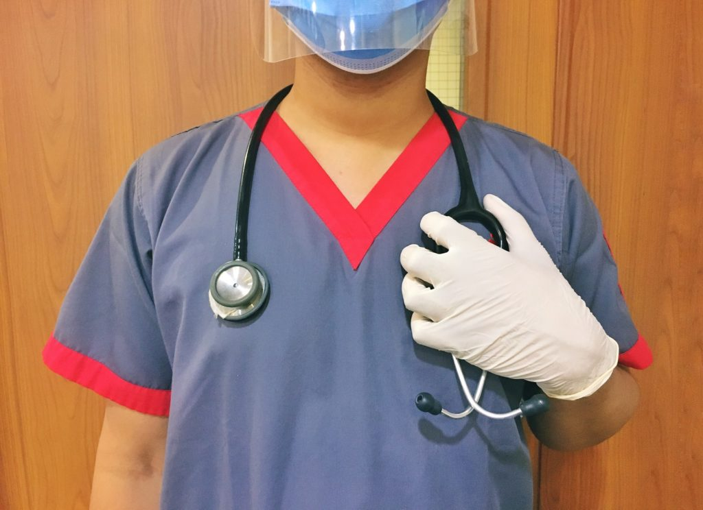 Person in a mask and gloves with a stethoscope around their neck