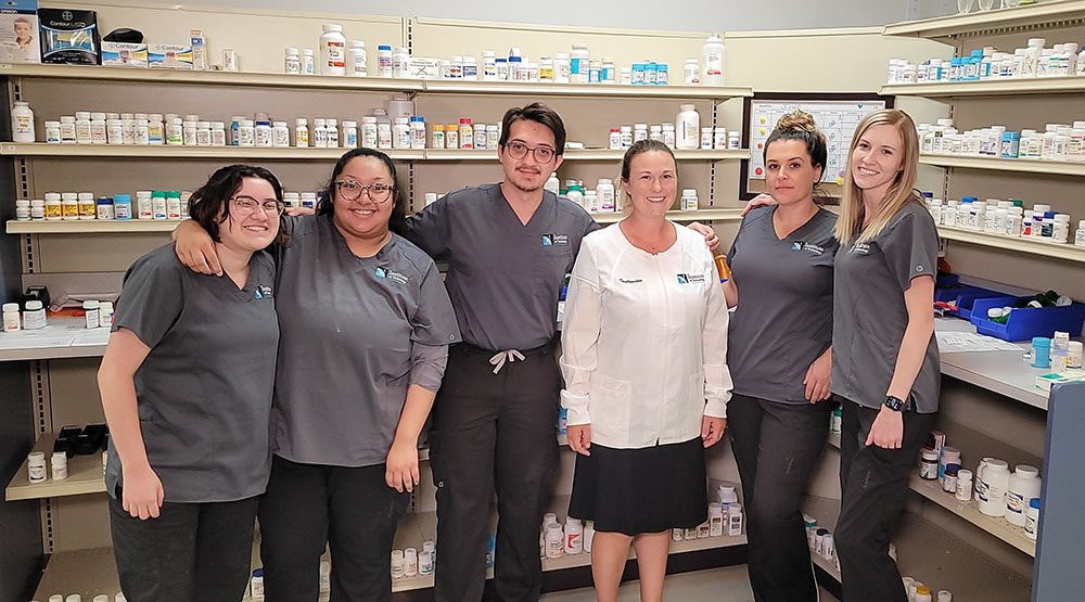 Pharmacy professor and students gathered in front of shelves of medicine smiling