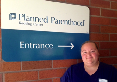 Woman smiling in front of Planned Parenthood entrance